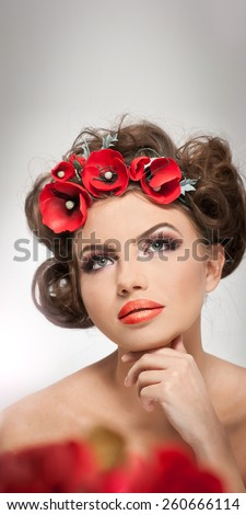 Portrait of beautiful girl in studio with red flowers in her hair and naked shoulders. Sexy young woman with professional makeup and bright flowers. Creative hairstyle and makeup, studio shot - stock photo