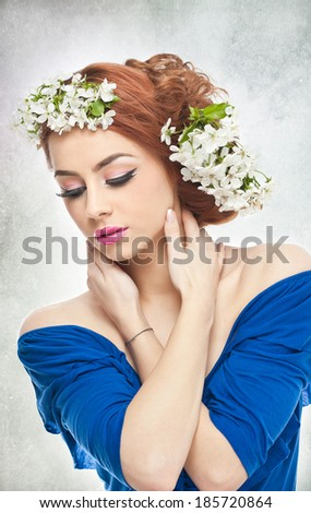 Portrait of beautiful girl in studio with spring flowers in her hair. Sexy young woman in blue with bright white flowers. Creative hairstyle and makeup, fashion photo studio shot - stock photo
