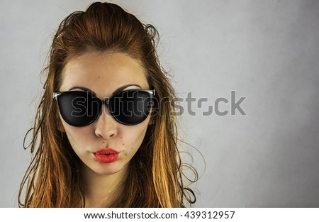 Portrait of beautiful girl in sunglasses on light background