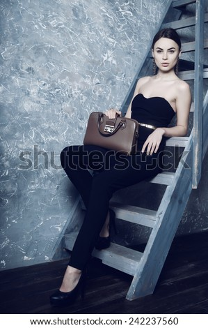 Portrait of beautiful girl in the studio sitting on the stairs, holding bag - stock photo