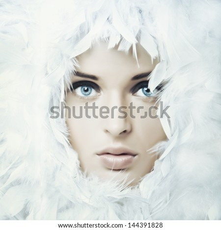 Portrait of beautiful girl in white feathers - stock photo