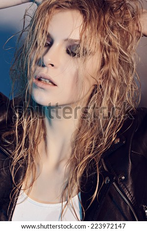 Portrait of beautiful girl rocker in studio with wet hair and eyes closed, close-up