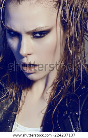 Portrait of beautiful girl rocker in studio with wet hair, close-up