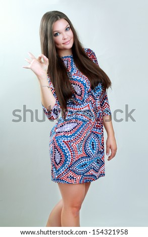 Portrait of beautiful girl showing OK sign and smiling, over grey background  - stock photo
