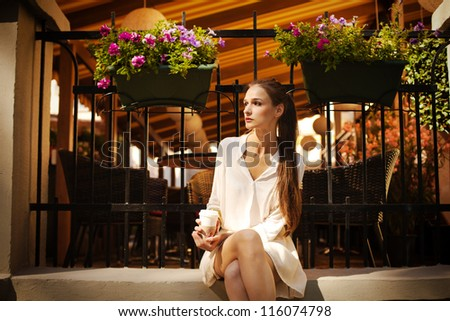 Portrait of beautiful girl sitting at the cafe on the street - stock photo