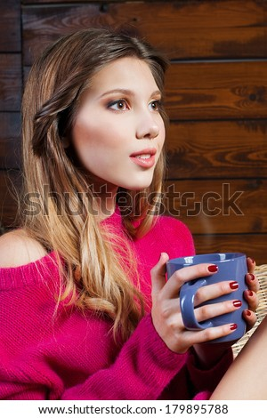 Portrait of beautiful girl sitting in a chair and holding a coffee cup, wooden wall as a background - stock photo