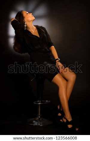 Portrait of beautiful girl sitting in a chair in an evening dress