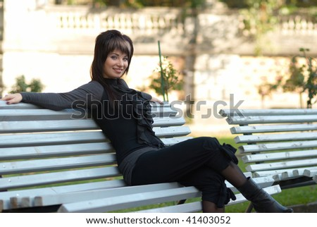 Portrait of beautiful girl sitting on the bench - stock photo