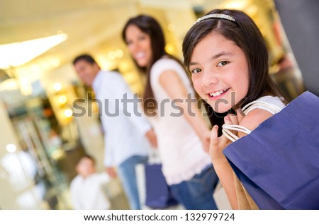 Portrait of beautiful girl smiling and shopping with her family - stock photo