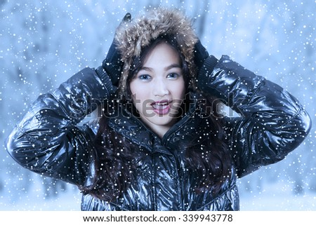 Portrait of beautiful girl standing outdoors and looking on the camera while wearing winter jacket