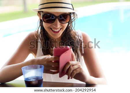 Portrait of beautiful girl taking a mobile phone at the swimming pool. - stock photo