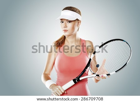 Portrait of beautiful girl tennis player with a racket on grey background. Tennis advertisement. - stock photo