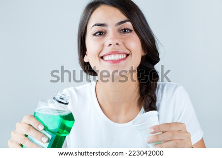 Portrait of beautiful girl using mouthwash. Isolated on white. - stock photo