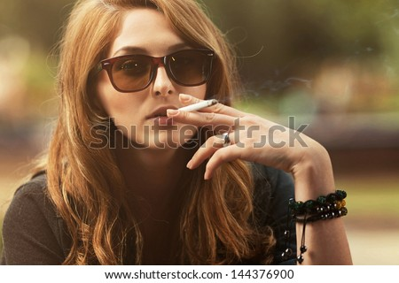 Portrait of beautiful girl wearing glasses and smoking a cigarette