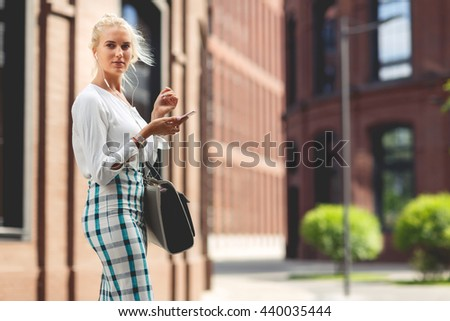 Portrait of beautiful girl with a phone in her hands - stock photo