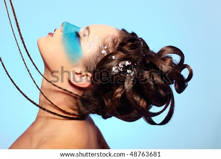 portrait of beautiful girl with blue stripe facial bodyart and fantasy hair-do with several thin braids