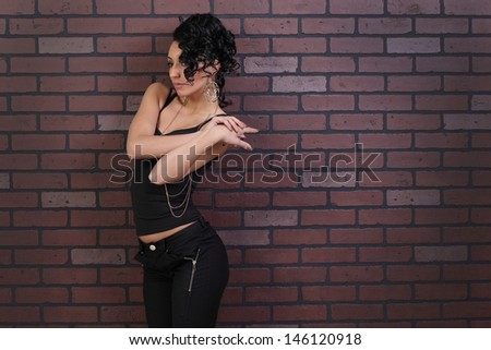 portrait of beautiful girl with curly hair and art make-up on a background a brick wall