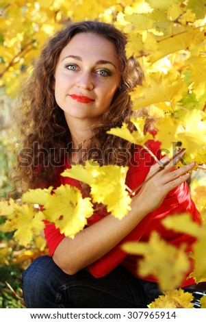 Portrait of beautiful girl with curly hair in yellow grape vineyard