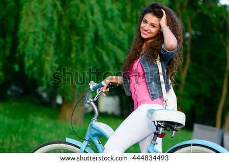 Portrait of beautiful girl with curly hair riding on a bicycle in the park in the summer in the city. Outdoor portrait