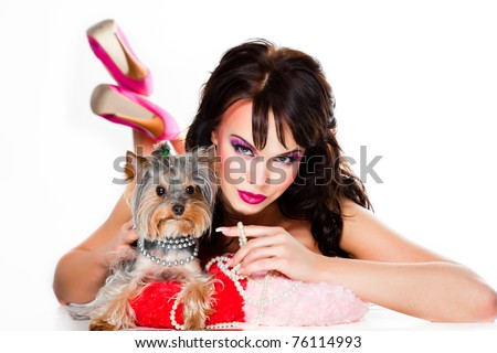 Portrait of beautiful girl with dark long curly hair and vibrant make up wearing pink satiny ribbon holding small yorkshire terrier on white background - stock photo