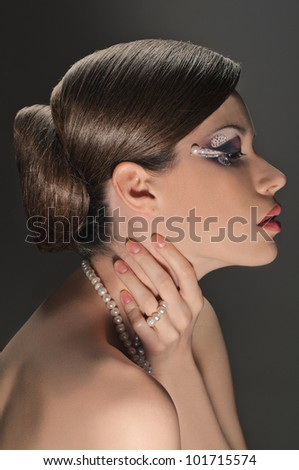 portrait of beautiful girl with elegant coiffure and art make up on grey - stock photo