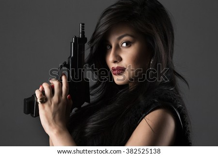 Portrait of beautiful girl with gun on dark background