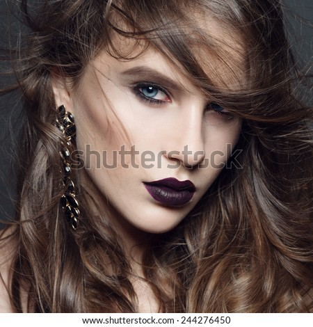 Portrait of beautiful girl with long curly hair in the studio in the Gothic style, closeup - stock photo