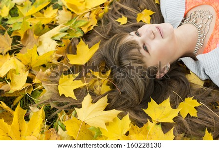 Portrait of beautiful girl with long hair in autumn park