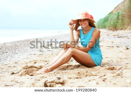 Portrait of beautiful girl with long legs posing on the beach - stock photo