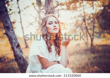 portrait of beautiful girl with magic eyes in wreath and dress in the forest outdoor. Bright witch, druid, shaman. book cover - stock photo