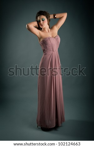 Portrait of beautiful girl with pink dress against dark background.