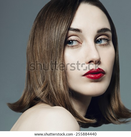 Portrait of beautiful girl with red lipstick in the studio on a gray background