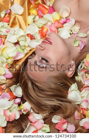 portrait of beautiful girl with rose petals - stock photo