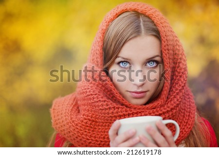 Portrait of beautiful girl with scarf and cup with hot drink in autumn nature - stock photo