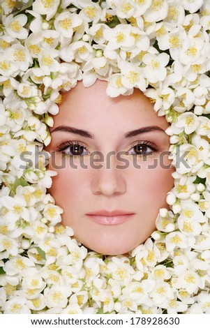 Portrait of beautiful girl with stylish makeup and flowers around her face - stock photo