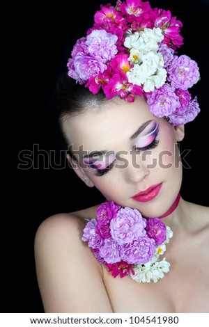 Portrait of beautiful girl with stylish makeup and pink flowers around her