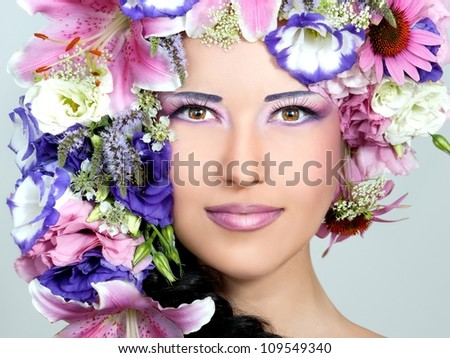 Portrait of beautiful girl with stylish makeup and violet flowers around her - stock photo