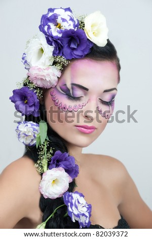 Portrait of beautiful girl with stylish makeup and violet flowers around her