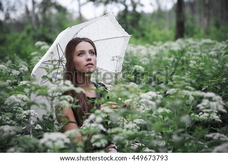 Portrait of beautiful girl with umbrella in nature and white flowers
