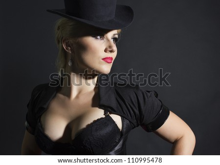 Portrait of beautiful girl, woman in hat cylinder and coat on black background