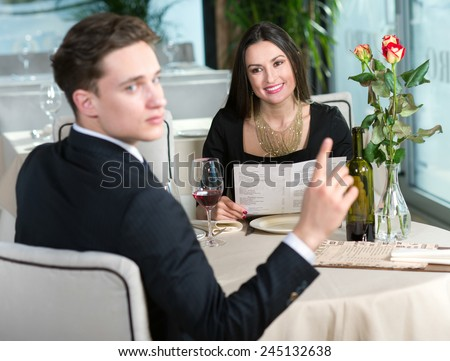 Portrait of beautiful girls sitting in restaurant together with her husband and drinking wine - stock photo