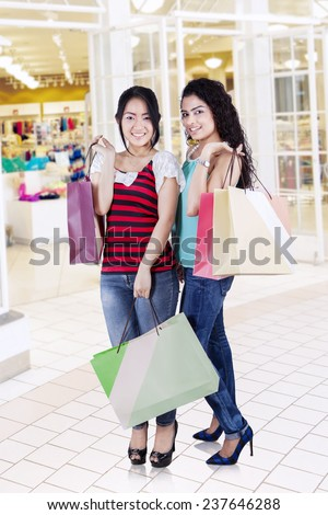 Portrait of beautiful girls standing in the shopping center while holding shopping bags and smiling at the camera - stock photo
