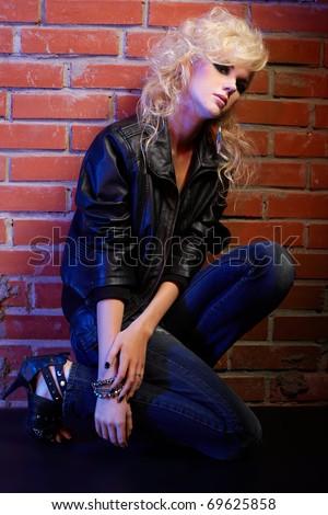 portrait of beautiful glam rock style blonde girl sitting near red brick wall - stock photo