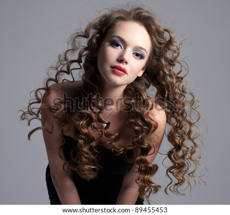 Portrait of beautiful glamour  girl with long curly hair - grey background - stock photo