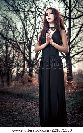 Portrait of beautiful goth girl amongst the trees - stock photo