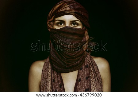 Portrait of beautiful green-eyed woman in hijab on black background - stock photo