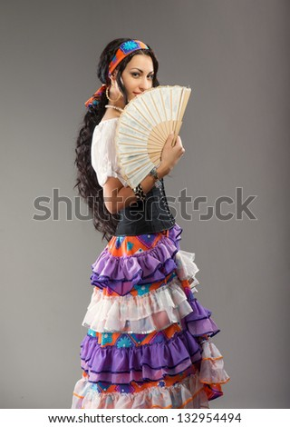 Portrait of beautiful Gypsy girl with fan, on gray background - stock photo