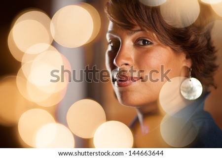 Portrait of beautiful happy African American woman, closeup. View through illuminated bokeh circles. - stock photo