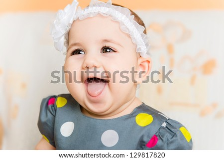 Portrait of beautiful happy baby girl with white flower on head - stock photo