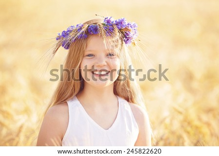 Portrait of beautiful happy blond, Caucasian with blue eyes smiling. Teenager with flowers crown in wheat field.  - stock photo